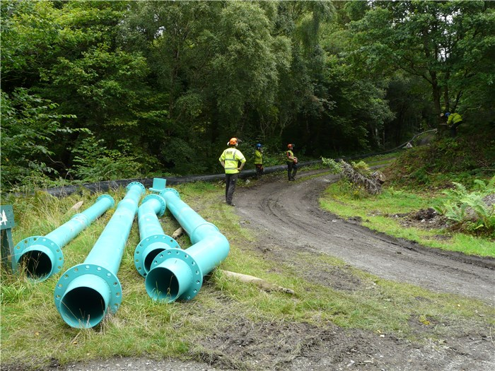 Steel pipe ready for installation down the slope to the turbine house and Alfa Tree Services carrying out some final clearance 24 Aug 2015